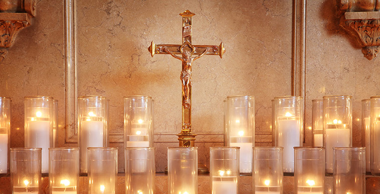 A cross behind two rows of candles